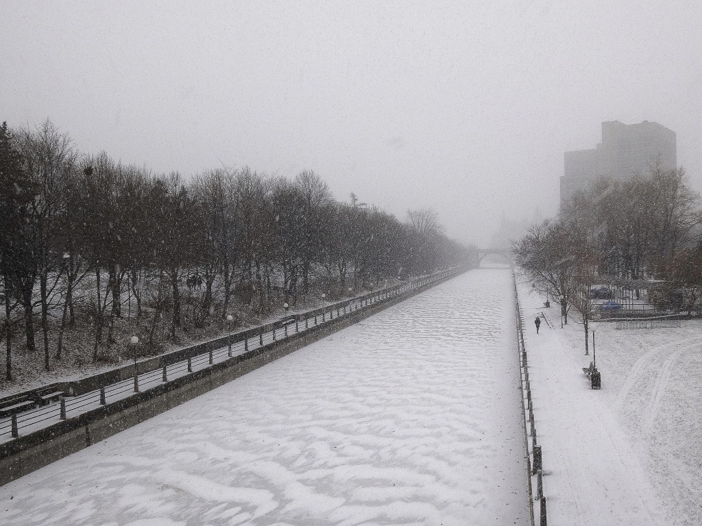 A winter scene from the Corkstown Bridge, with snow blowing and drifting on the frozen Rideau Canal