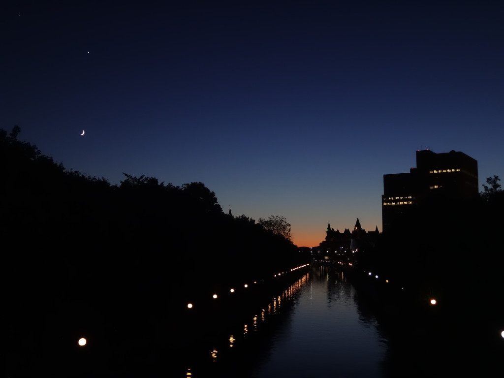 Twilight on the Corkstown Footbridge. A bright planet and crescent moon hang in a dark, navy-blue sky. A faint orange glow lingers behind the distant Gatineau Hills.