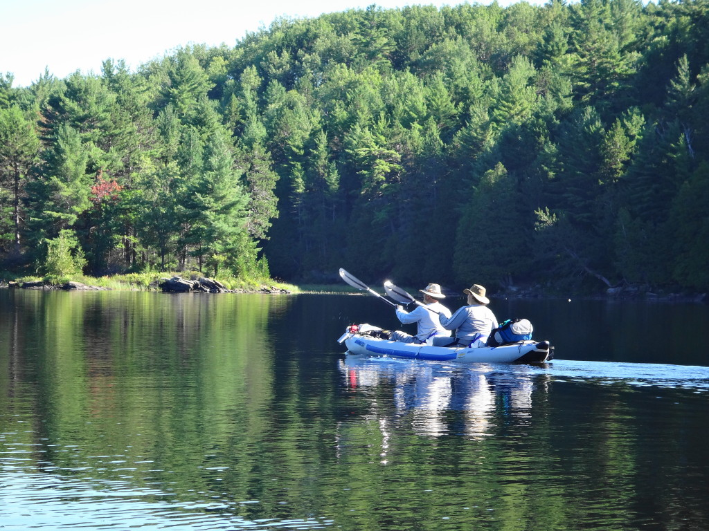 Two people paddle across a calm lake in an inflatable kayak, with a pine-covered shoreline in the background.
