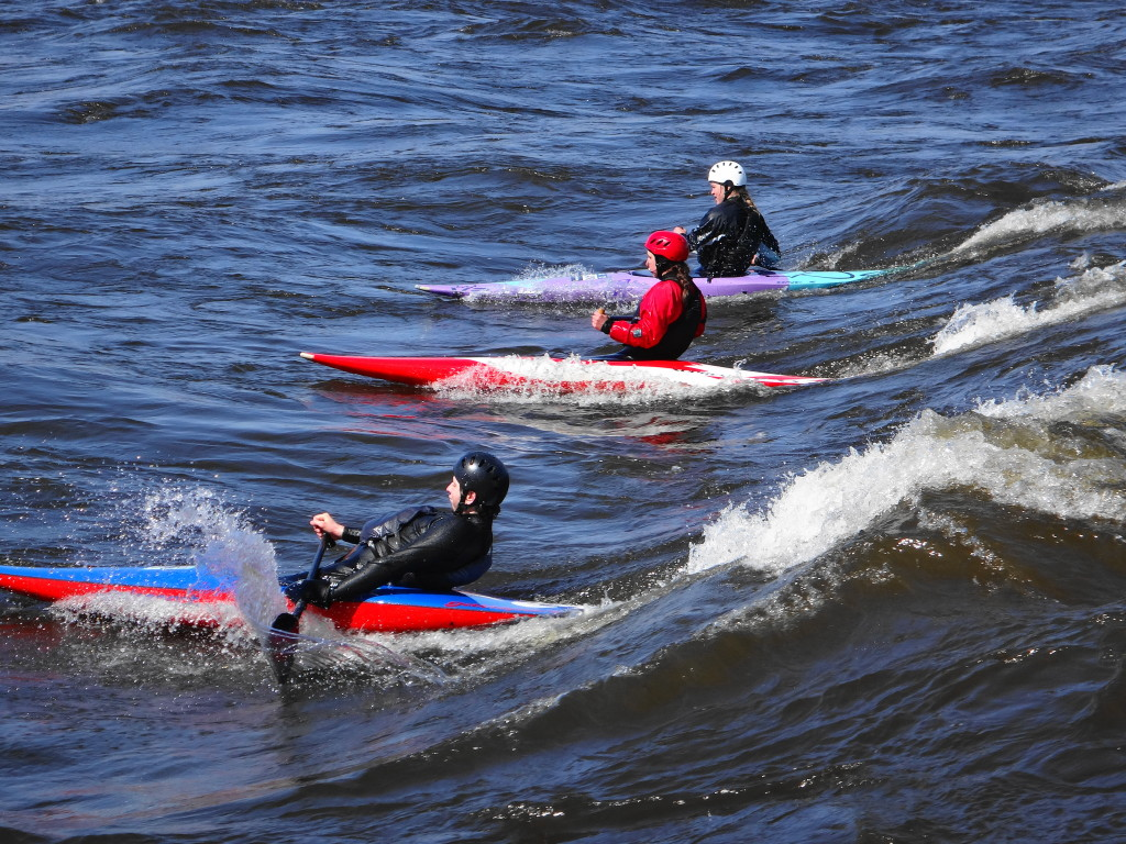 Three whitewater canoes slice down a standing wave.  Their canoes and their paddles throw up spray in the swiftly moving water.