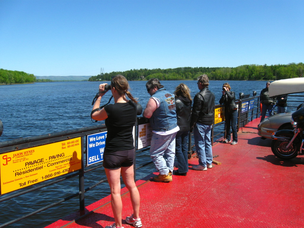 A group of people look out over the Ottawa River from the deck of the Quyon Car Ferry.