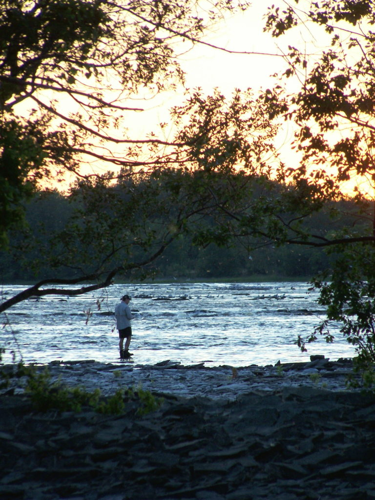 A fishermen casts into the Ottawa River near Mud Lake at sunset.