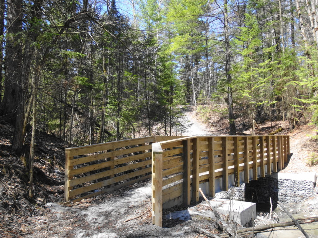 A footbridge for a multi-use trail crosses Bilberry Creek.
