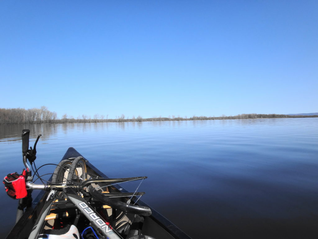 The bow of a canoe cuts through glassy water at Shirley's Bay. A bicycle lies in the canoe.