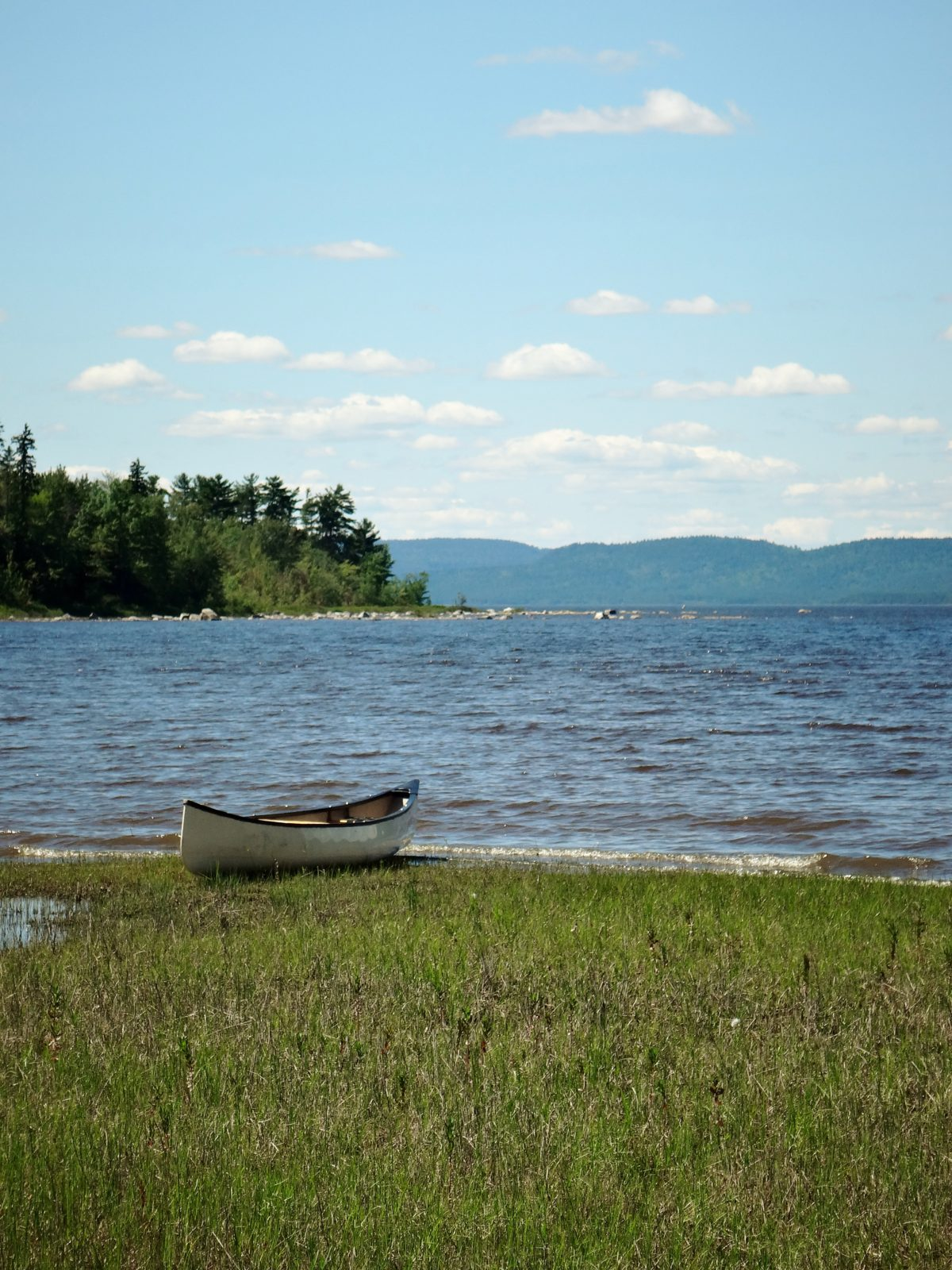 A canoe rests sandy shoreline, with the Ottawa River in the background.