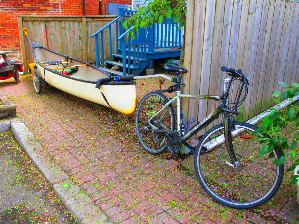 A canoe rests on a towed trailer behind a bicycle.