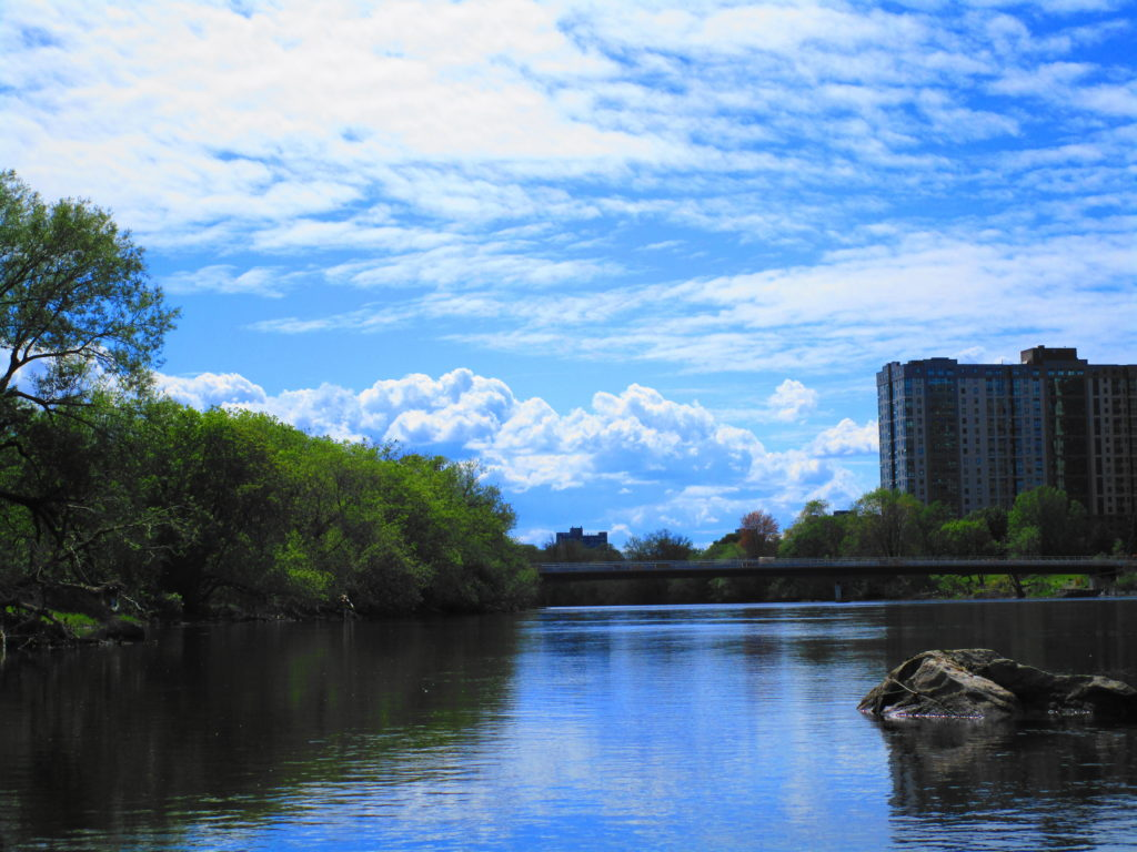 A blue sky and fair weather clouds hang over the Rideau River and the Hurdman Transit Bridge.