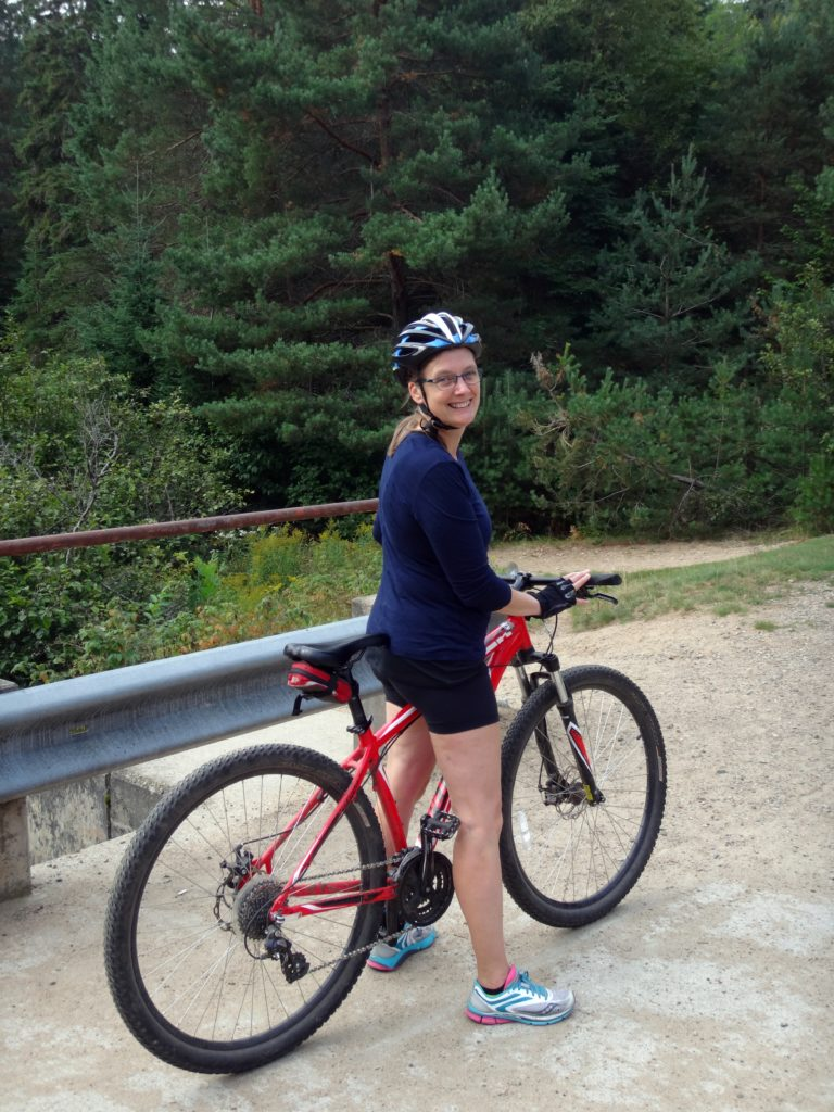 A woman stands astride a mountain bike on the Old Railway Bike Trail in Algonquin Park.