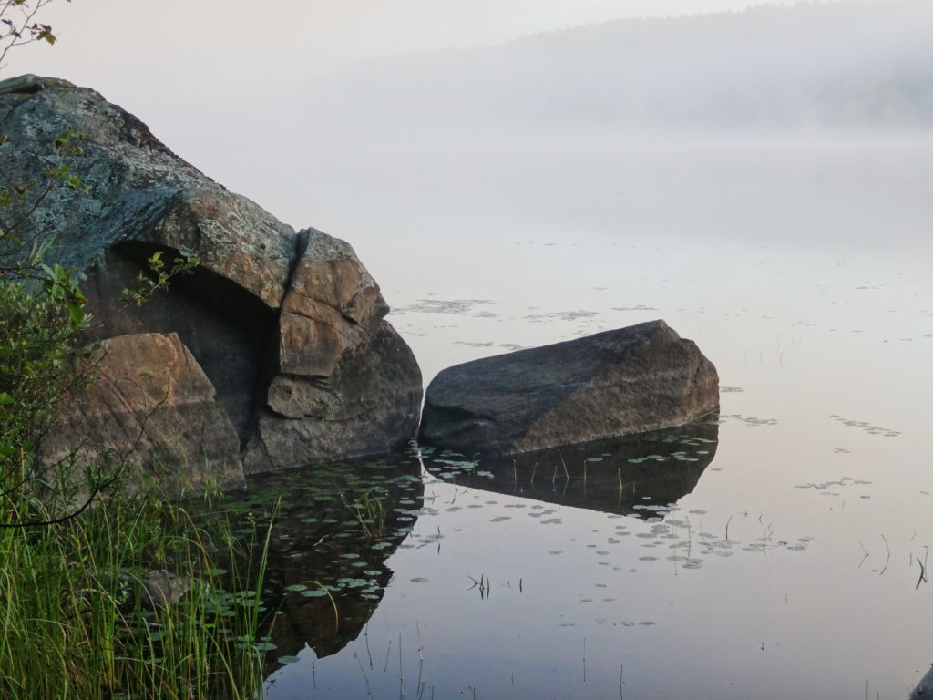 In the early morning, the glassy waters of St. Andrew's Lake reflect lichen-encrusted boulders.